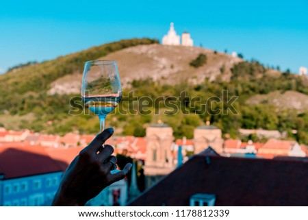 Awesome picture of wine glass with the reflection and the chapel on holy hill on the background.