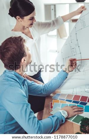Wait a second. Pretty brunette raising arm while demonstrating blueprint #1178877010