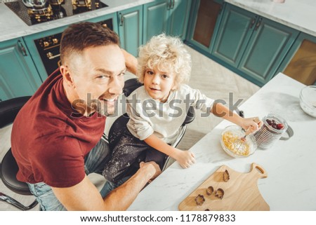 Joining father. Handsome curly blonde-haired son feeling excited while joining his father cooking fruit pie #1178879833