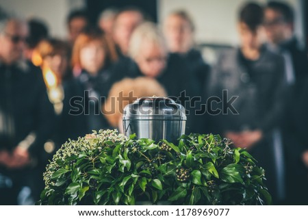 A metal urn with ashes of a dead person on a funeral, with people mourning in the background on a memorial service. Sad grieving moment at the end of a life. Last farewell to a person in an urn. #1178969077
