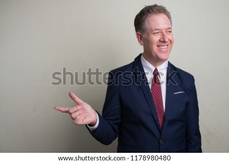 Portrait of mature businessman against white background Royalty-Free Stock Photo #1178980480