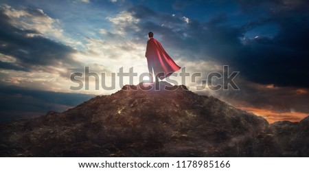 Businessman in a suit and cape hero on top of a mountain,Business Success concept. Royalty-Free Stock Photo #1178985166