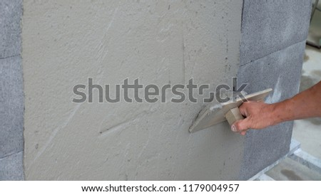 Construction worker is cementing on the wall. #1179004957