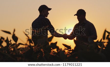 Two farmers talk on the field, then shake hands. Use a tablet Royalty-Free Stock Photo #1179011221