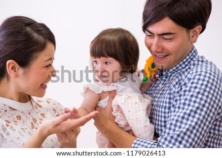 The girl who is held in their arm by parents #1179026413
