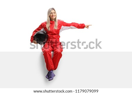 Female racer seated on a panel pointing isolated on white background #1179079099