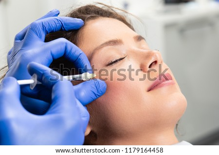 Attractive young woman is getting a rejuvenating facial injections. She is sitting calmly at clinic. The expert beautician is filling female wrinkles by hyaluronic acid. #1179164458