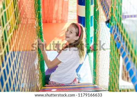 Beautiful little girl is playing in the children's playroom. #1179166633