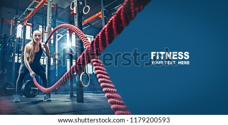 Woman with battle rope battle ropes exercise in the fitness gym. gym, sport, rope, training, athlete, workout, exercises concept #1179200593