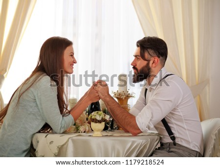 Young couple in love at table celebrates a romantic dinner holding hands #1179218524