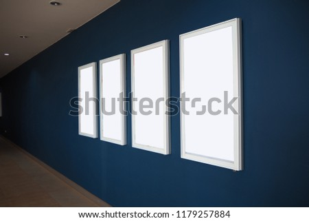 Four blank Advertisements Copyspace White Isolated Interior with hug blue background,Empty white poster,indoor paper,empty frames in a room against a blue wall