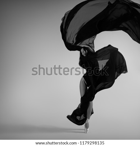 A ballerina posing with a black flying cloth. Black and white photo.
