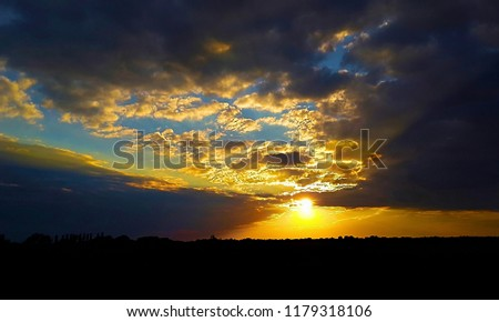 colorful sunset in the Ukrainian steppe, low clouds lush over the contrasting horizon line #1179318106