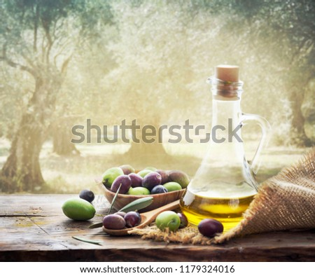 Olives and bottle of Extra virgin olive oil on wooden table in olive garden. Traditional homemade olive oil and olive trees with sunlight in background.  #1179324016