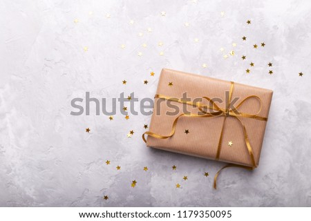 Gift box wrapped in craft paper with gold ribbon and stars on grey stone #1179350095