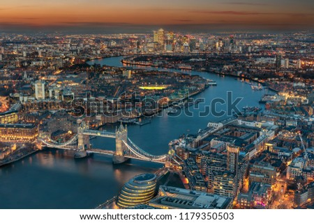 Aerial view of London: from the Tower Bridge along the rover Thames to the financial district Canary Wharf during evening time #1179350503