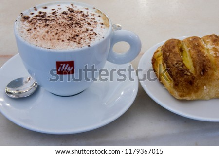 Sweet breakfast with cappuccino in a ceramic cup and apple brioches. Coffee and whole milk assembled Turin Italy July 2018 #1179367015