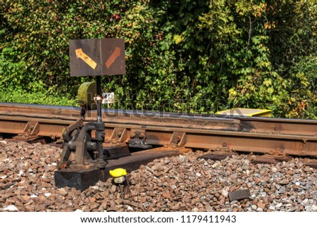 Old railway cross switch covered with black oil and dirt. Rail tracks and green bushes in background. #1179411943