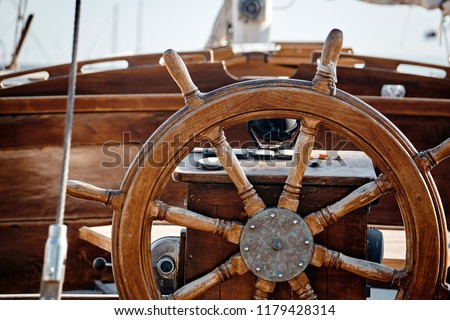 Closeup of a wheel and deck of a wooden antique sailing yacht. Royalty-Free Stock Photo #1179428314