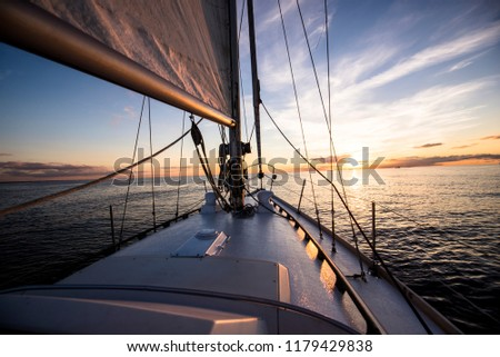 White sloop rigged yacht sailing at sunset.A view of the deck, bow, mast and sails. Baltic sea, Latvia. Transportation, nautical vessel, cruise, sport, regatta, recreation, leisure activity Royalty-Free Stock Photo #1179429838