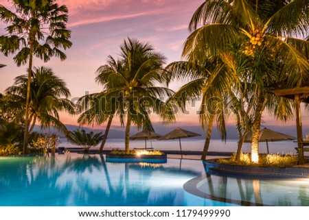 luxury swimmingpool on the beach during sunset with palms and reflections in the water, bali #1179499990