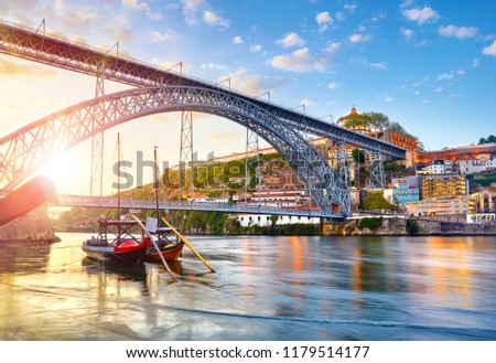 Porto old town, Portugal. Evening sunset with sunshine. Panoramic view at Ponte de Dom Luis on Douro river. Medieval monastery fort Mosteiro da Serra do Pilar. Traditional boats with port wine. #1179514177