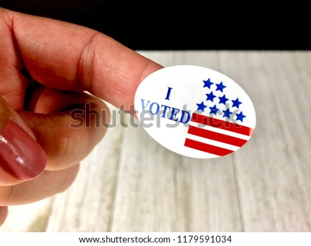 I voted sticker on a woman's finger #1179591034