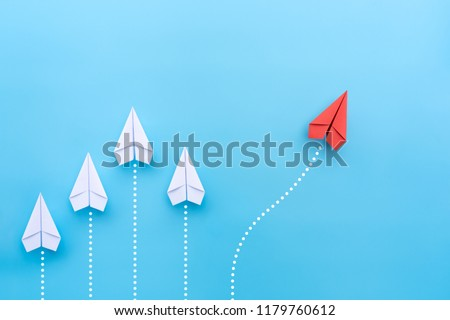 Group of white paper planes in one direction and one red paper plane pointing in different way on blue background. Business for new ideas creativity and innovative solution concepts. #1179760612