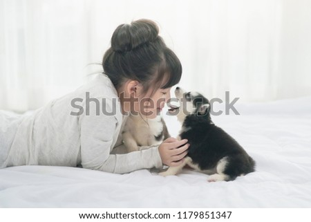 Little asian girl lying with  siberian husky puppy on bed #1179851347