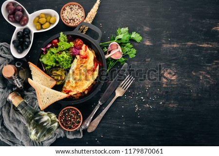 Omelet with vegetables and mushrooms in a frying pan. On a wooden background. Free space for text. Top view. #1179870061