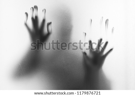 Shadow blur of horror man.Hands on the glass.Dangerous man behind the frosted glass.Mystery man.Halloween background.Black and white picture.Blur picture