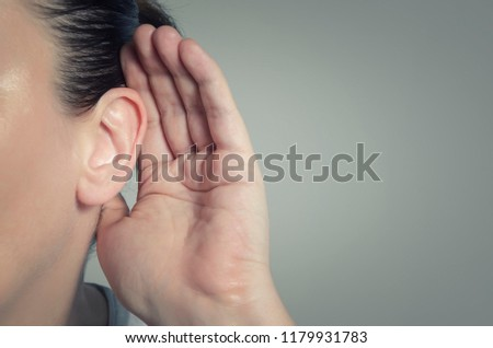 Woman with hand on ear listening for quiet sound or paying attention Royalty-Free Stock Photo #1179931783