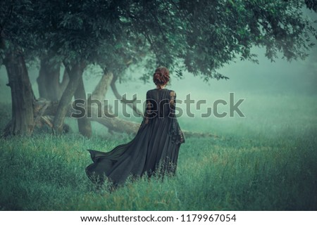 fantasy ghost girl walk dark nature forest long black vintage dress train waving fly wind. Art Gothic queen witch.  trees fog. artwork mysterious silhouette beautiful young woman medieval silk clothes Royalty-Free Stock Photo #1179967054