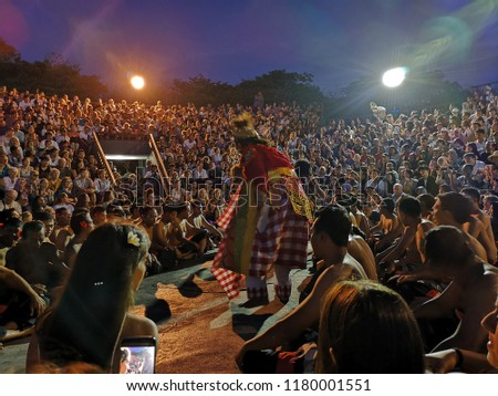 Bali, Indonesia- Sept 13, 2018:Tourists watch traditional Balinese Kecak Dance at Uluwatu Temple on Bali, Indonesia. Kecak (also known as Ramayana Monkey Chant) is very popular cultural show on Bali. #1180001551