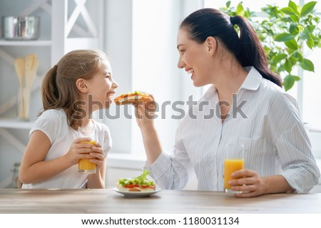 Healthy food at home. Happy family in the kitchen. Mother and child daughter are having breakfast. #1180031134
