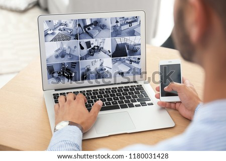 Man using laptop for monitoring CCTV cameras at table indoors. Home security system #1180031428