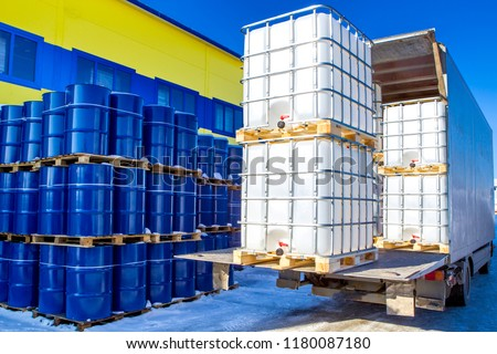 Discharge of plastic barrels. Barrels for the chemical industry. Blue metal barrels. White plastic containers. Chemical industry. The machine brought chemical substances. #1180087180