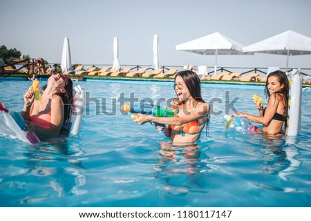Cheerful and funny models playing in swimming pool. They hold water guns in hands and using it. Two woman are against third. They smile and laugh #1180117147