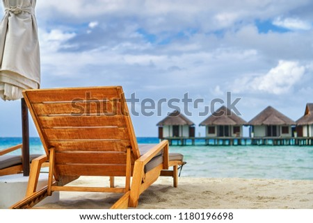 Water Villas (Bungalows) on the Perfect Tropical Island, Beautiful white sand on Tropical beach blue water blue sky a chair and umbrella , Velassaru- Maldives islands  #1180196698