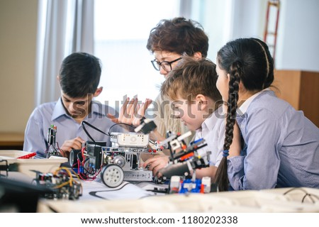Never getting bored together. Adorable youngsters sitting at a table with their teacher and learning programming process of their new robot. #1180202338