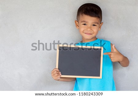 Portrait of Asian boy holding a black board and happy. concept back to school