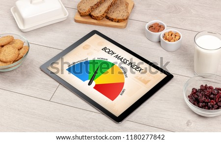 Healthy food with tablet on a wooden background with words Body Mass Index. Health concept. #1180277842