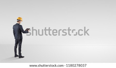 Young architect with construction helmet standing in an empty space and holding a plan #1180278037