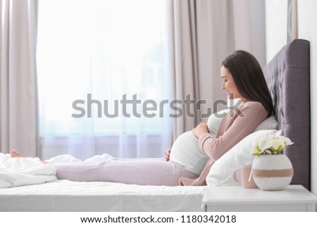 Young beautiful pregnant woman lying on bed and touching her belly at home #1180342018
