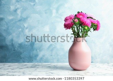Vase with beautiful aster flower bouquet on table against color background. Space for text #1180353397