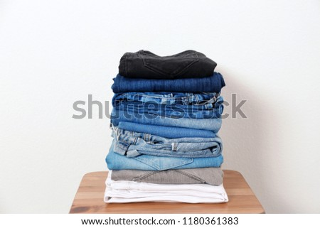 Stack of different jeans on table against white background #1180361383