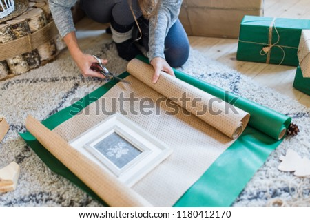 Mother wrapping christmas gifts for family. Preparing christmas gifts. Home living room in scandinavian style #1180412170