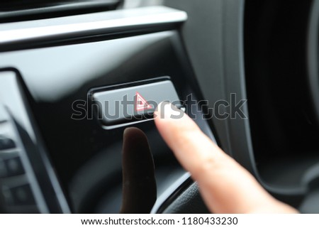 Finger hitting button emergency in the car. #1180433230