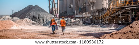 People are working in the industry. Modern technologies work at a cement plant. Technological work on the production of cement. Working atmosphere with copy space. Heaps of sand and soil raw materials #1180536172