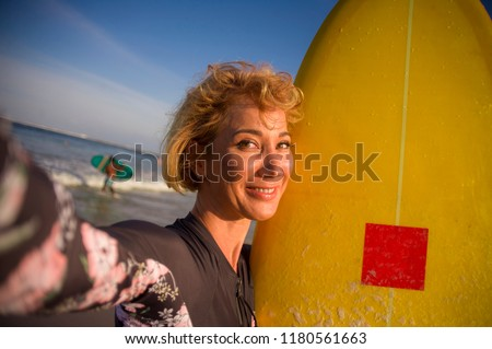 young attractive and happy blonde surfer woman in swimsuit holding surf board in the beach taking self portrait selfie picture smiling cheerful enjoying holidays at tropical island